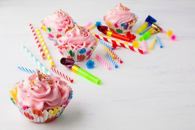 Roze cupcakes en kaarsen verjaardag achtergrond Premium Foto
