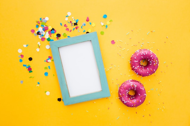Roze doughnut en frame met copyspace op gele achtergrond Gratis Foto