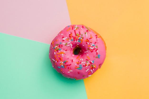 Roze doughnut op gekleurde achtergrond Gratis Foto