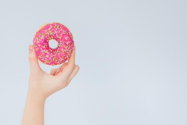 Roze doughnut ter beschikking op een grijze muurachtergrond Premium Foto