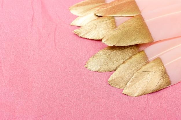 Roze en gouden veren op roze Premium Foto