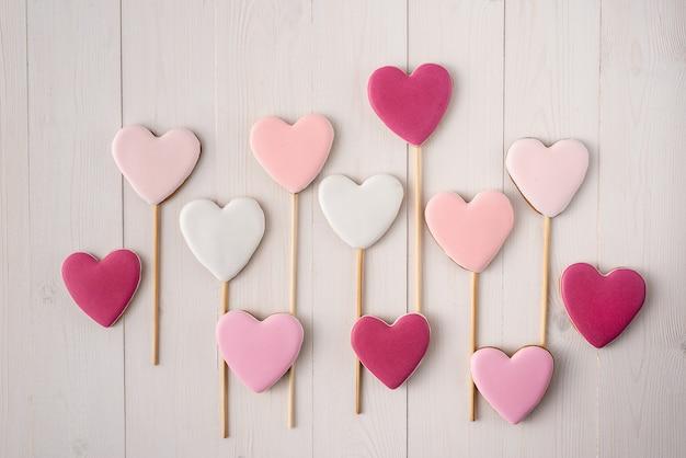 Roze en witte koekjes op een stok in de vorm van harten. valentijnsdag. Premium Foto