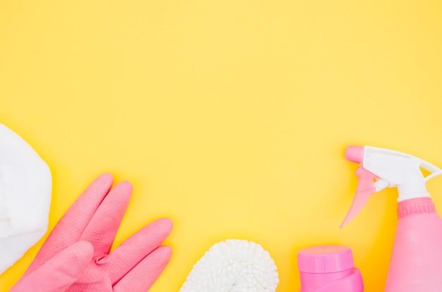 Roze en witte schoonmakende levering op gele achtergrond Gratis Foto