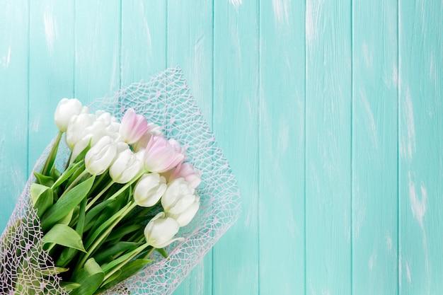 Roze en witte zeer tedere tulpen op groen blauwe houten achtergrond Premium Foto