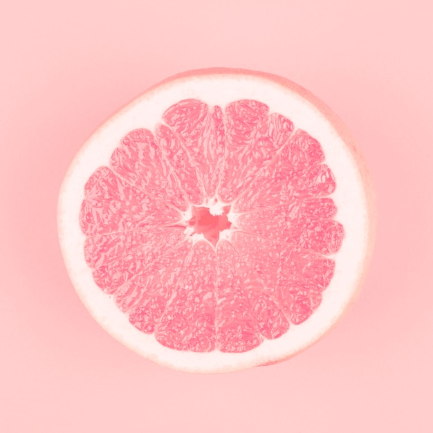 Roze gehalveerde verse sappige grapefruit op roze achtergrond Gratis Foto