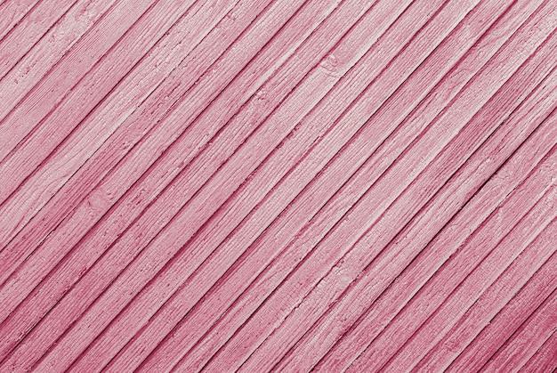 Roze gestructureerde achtergrond van diagonaal gerangschikte houten planken met gebarsten verf textuur Premium Foto