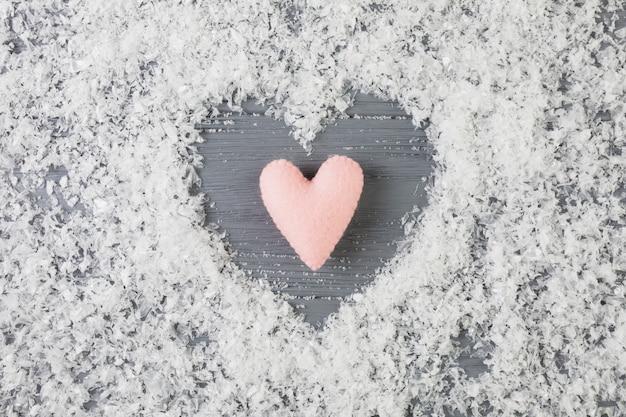 Roze hart tussen decoratieve sneeuw op houten bureau Gratis Foto