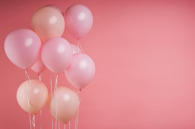 Roze helium verjaardagsballons op roze studio Premium Foto