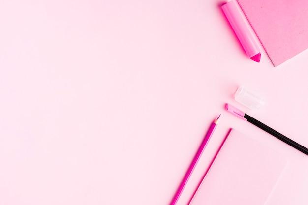 Roze kantoorhulpmiddelen op bureau Gratis Foto