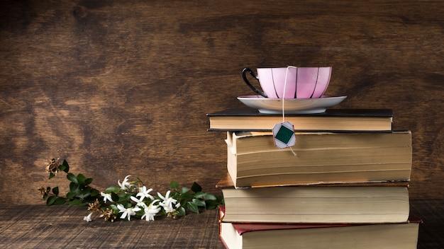Roze keramische kop en schotel op de stapel boeken in de buurt van de witte bloemen en bladeren op houten bureau Gratis Foto