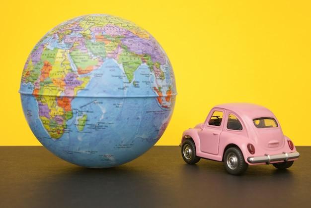 Roze kleine retro auto met bol van de wereldbol. Premium Foto