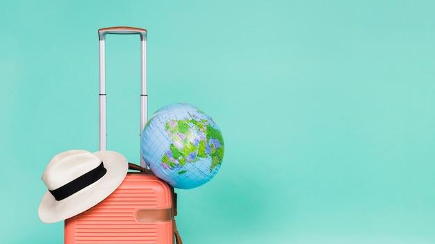 Roze koffer met hoed en wereldbol erop Gratis Foto
