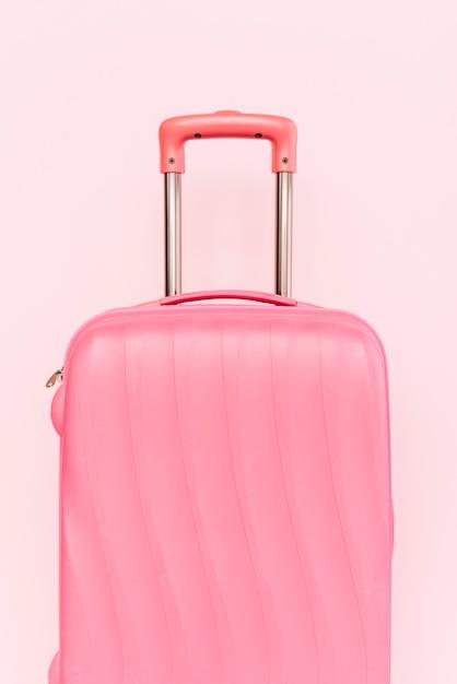 Roze koffer voor reizen tegen roze achtergrond Premium Foto