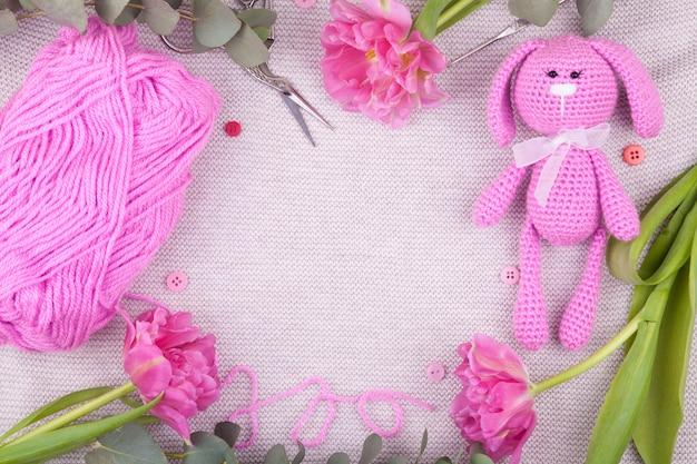 Roze konijn met tulpen. st. valentijnsdag decor. gebreide speelgoed, amigurumi, creativiteit Premium Foto