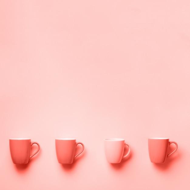 Roze kopjes over koraal kleur achtergrond. bovenaanzicht Premium Foto
