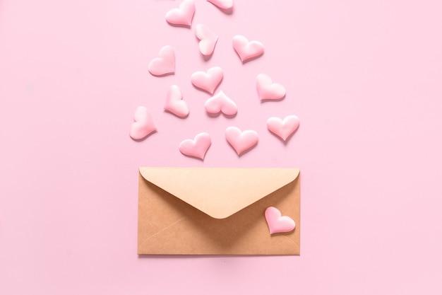 Roze liefdeharten van envelop op roze achtergrond. valentijnsdag wenskaart met kopie ruimte. Premium Foto