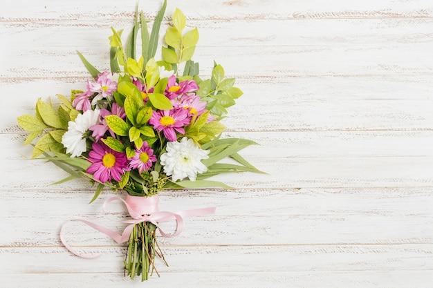 Roze lint gebonden met bloemboeket op houten bureau Gratis Foto