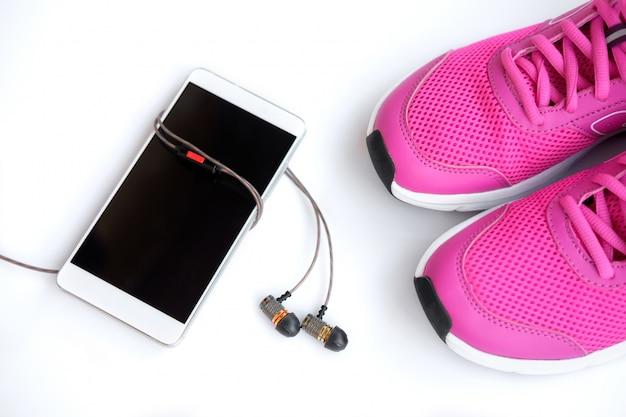 Roze loopschoenen voor vrouwen, telefoon en koptelefoon op een wit Premium Foto