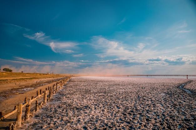 Roze meer en zandstrand met een zee baai onder een blauwe lucht met wolken Premium Foto