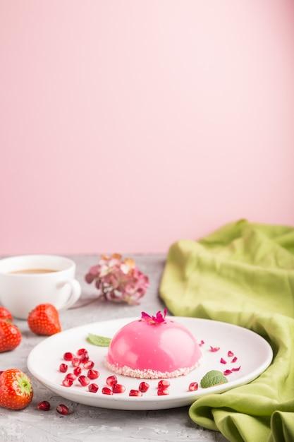 Roze mousse cake met aardbei en een kopje koffie Premium Foto