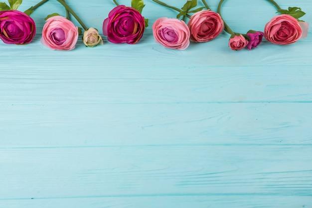 Roze nam bloemen toe die op houten lijst worden verspreid Gratis Foto