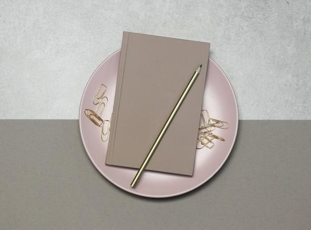 Roze notities met gouden potlood en clips op grijs Premium Foto