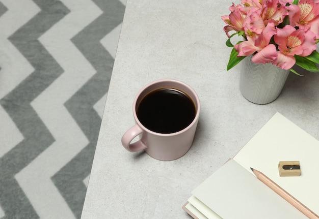 Roze notities papier, potlood, koffiekopje, bloemen geplaatst op grijze stenen tafel Premium Foto