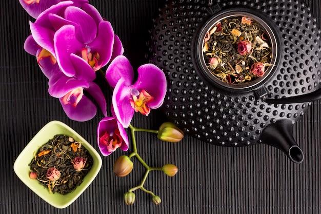 Roze orchideebloem en droog theekruid met textuur ceramische theepot op zwarte placemat Gratis Foto