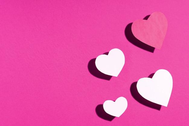 Roze paars papier harten op paarse oppervlak Premium Foto