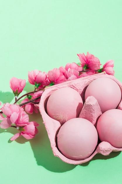 Roze paaseieren in rek met bloemen op tafel Gratis Foto