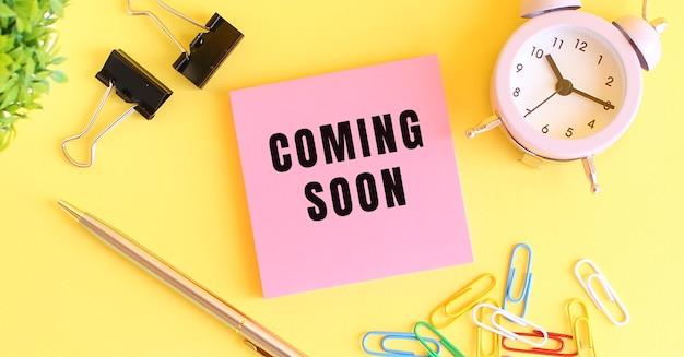 Roze papier met de tekst coming soon. klok, pen op een gele achtergrond. concept ontwerp. Premium Foto