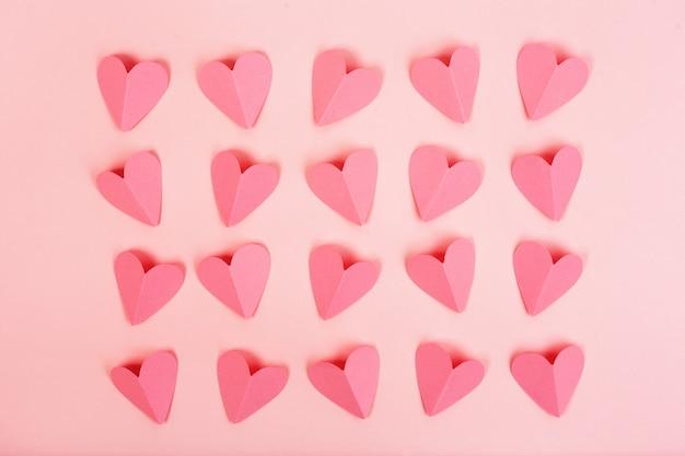Roze papieren harten gerangschikt in rijen op roze achtergrond Premium Foto
