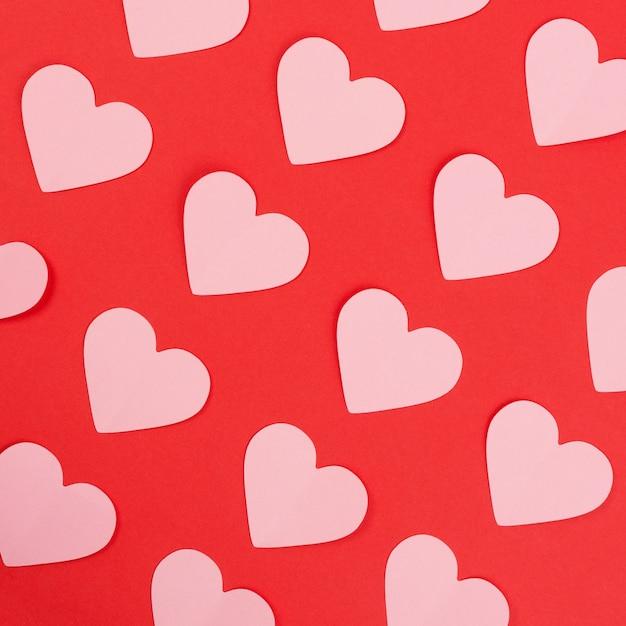 Roze papieren harten op rode achtergrond Premium Foto