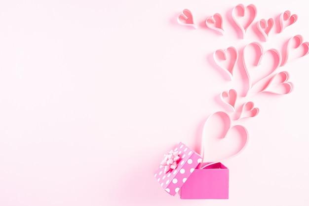 Roze papieren harten spatten uit geschenkdoos op roze pastel papier achtergrond Premium Foto
