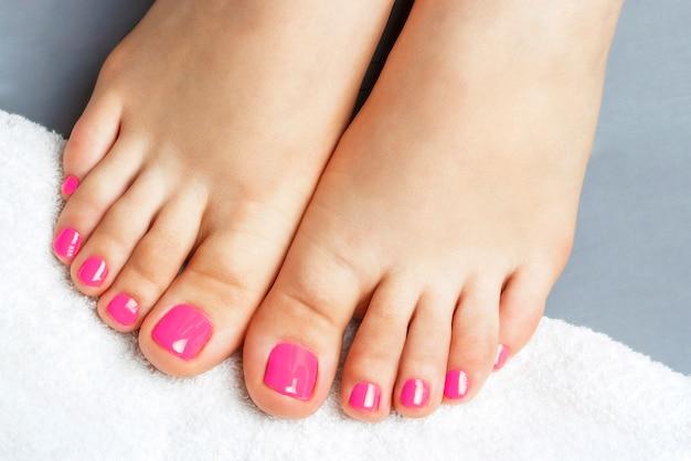 Roze pedicureclose-up, dat op grijs wordt geïsoleerd Premium Foto