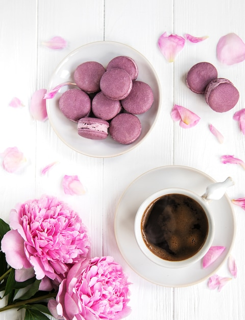 Roze pioenroos met koffie en macarons Premium Foto