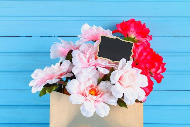 Roze pioenrozen in een ambachtelijke pakket met een schoolbord op een blauwe houten tafel. briefkaart voor de vakantie. Premium Foto