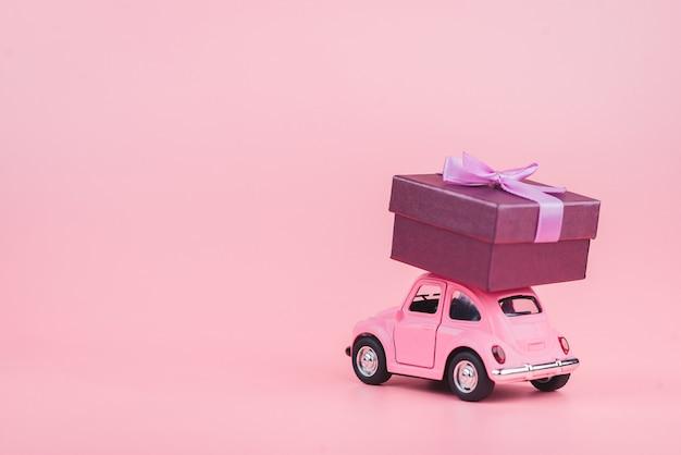 Roze retro speelgoedauto levert een geschenkdoos op roze achtergrond. 14 februari briefkaart, valentijnsdag. bloemen bezorgen. vrouwendag Premium Foto
