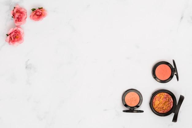 Roze roze bloemen en compact poeder op de hoek van witte achtergrond Gratis Foto