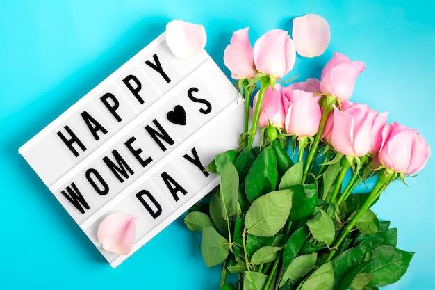 Roze rozen bloemen en lightbox met citaat gelukkige vrouwendag op blauwe achtergrond vlak leg Premium Foto