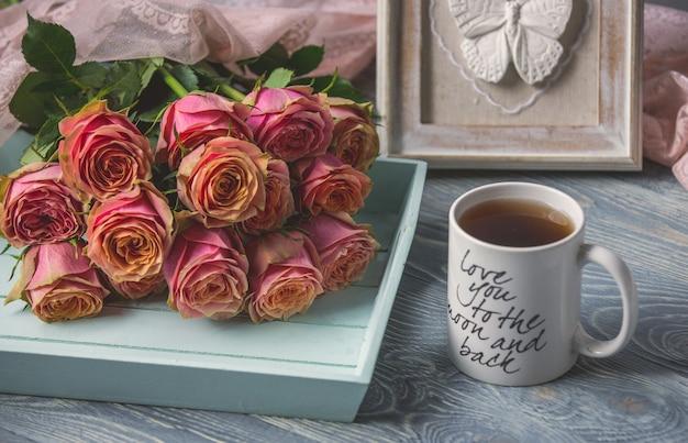 Roze rozen en een witte kop thee met liefdecitaat erop Gratis Foto