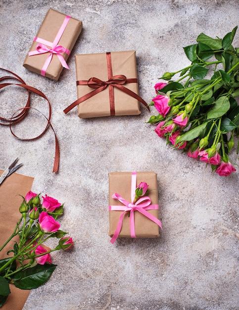 Roze rozen en geschenkdozen met linten Premium Foto