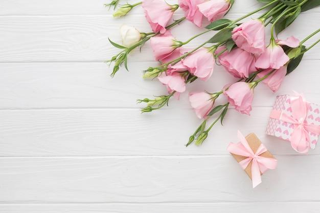Roze rozen en geschenken dozen op houten achtergrond Gratis Foto