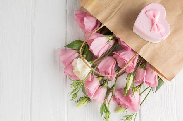Roze rozen in een papieren zak met geschenkdoos Gratis Foto