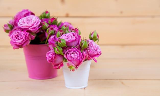 Roze rozen in een vaas op houten achtergrond en Premium Foto