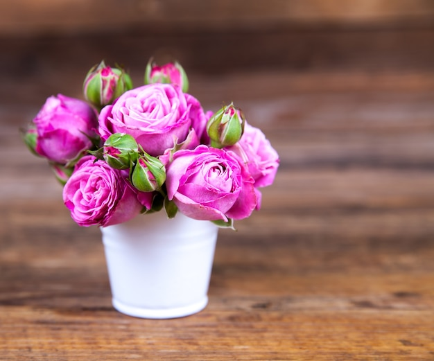 Roze rozen in een vaas op houten tafel Premium Foto