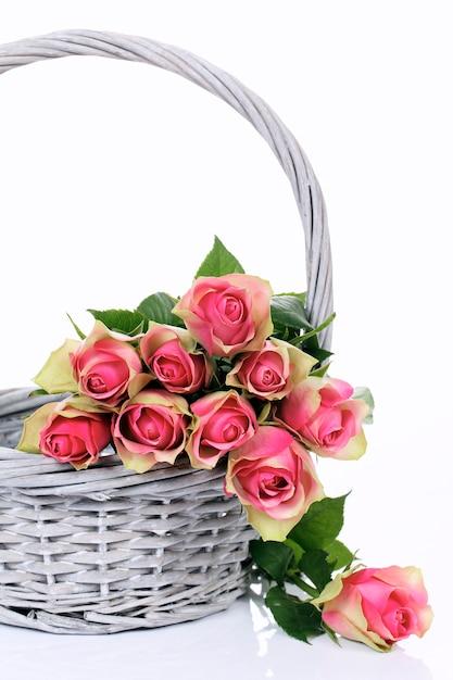 Roze rozen in mand op witte achtergrond Gratis Foto