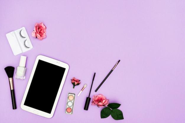 Roze rozen met digitale tablet en make-upborstels op purpere achtergrond Gratis Foto