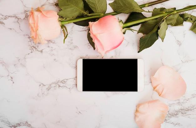 Roze rozen met slimme telefoon op marmeren gestructureerde achtergrond Gratis Foto