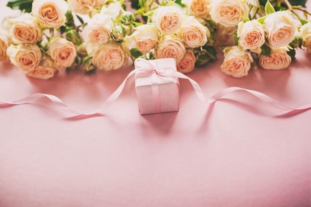 Roze rozenbloemen en gift of huidige doos roze achtergrond. Premium Foto